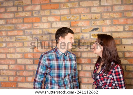 Young Smiling Couple Wearing Plaid Shirts Facing Each Other and Standing in front of Brick Wall - stock photo