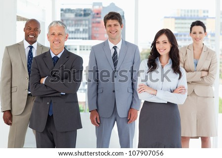 Young smiling executive standing in the middle of the room among his colleagues - stock photo