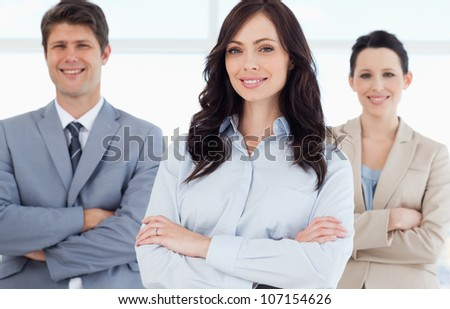 Young smiling executive woman crossing her arms in front of co-workers - stock photo