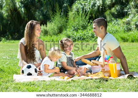 Young smiling family of four having picnic at meadow at summer day
