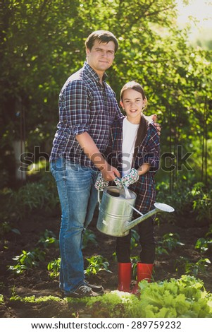 Young smiling father watering garden with little daughter