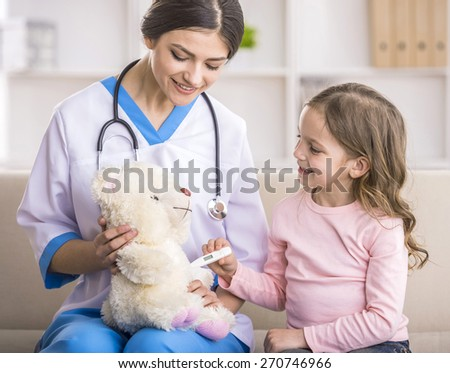 Young smiling female doctor and her little patient  with teddy bear. - stock photo
