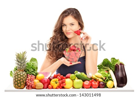 Young smiling female holding a bowl of strawberries and posing behind a table full of vegatebles and fruits isolated on white