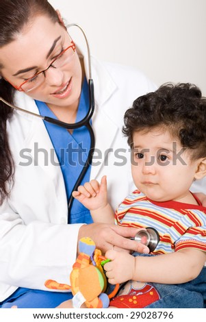 young smiling female pediatrician examining the baby boy - stock photo