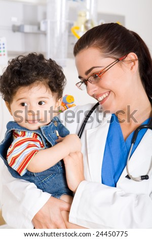 young smiling female pediatrician holding a cute baby boy