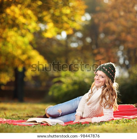 Young smiling female reading a book in a city park - stock photo