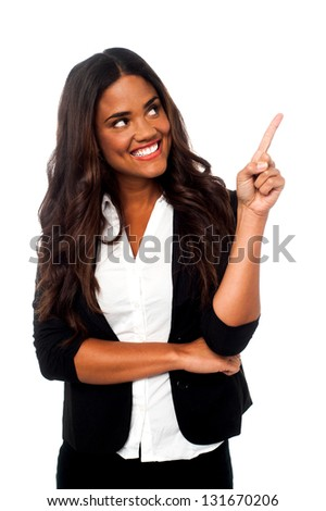 Young smiling female representative looking and pointing away. - stock photo