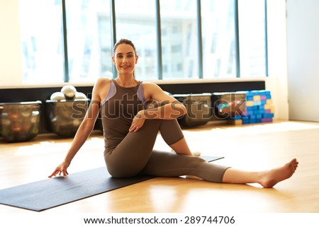 Young smiling female sitting and stretching her leg - stock photo