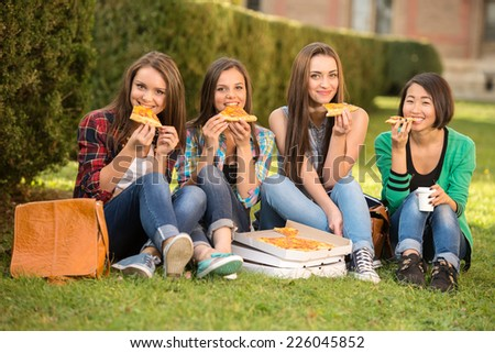 Young smiling female students are sitting on the ground, near a college, with pizza. - stock photo