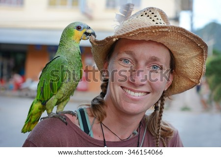 Young smiling female traveler with green parrot, Amazonia, Bolivia - stock photo