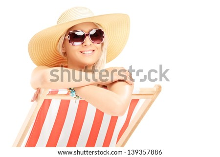 Young smiling female with a hat posing on a beach chair isolated on white background - stock photo