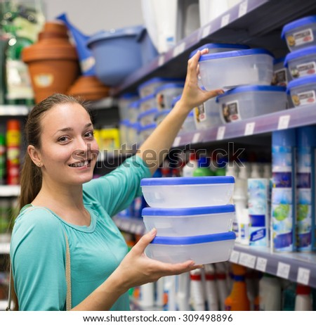 Young smiling girl choosing cruet-stands in the shop