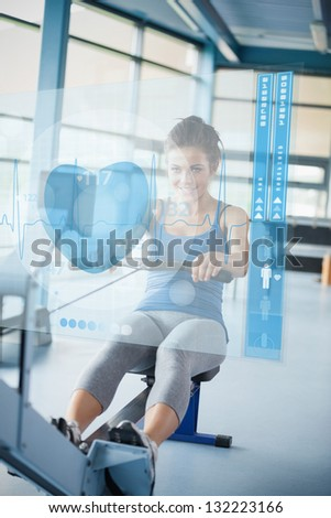 Young smiling girl doing rowing machine with futuristic interface - stock photo