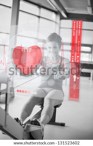 Young smiling girl doing rowing machine with futuristic interface in black and white - stock photo