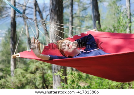 Young smiling girl enjoy on red hammock in forest. Relaxing on hammock with a smart phone. Redhead woman with freckles closed her eyes in pleasure. Forest, mountains in the background. - stock photo