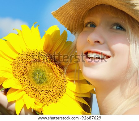 Young smiling girl holding ripe sunflower in her hands - stock photo