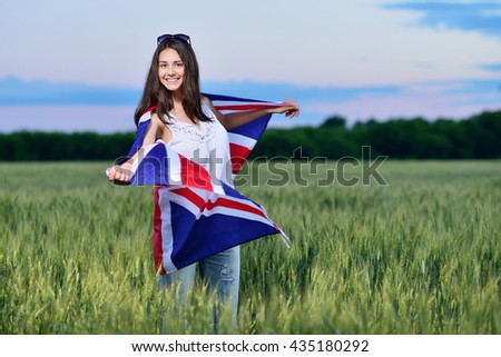 young smiling girl in a field of wheat. Flag of the Great Britain. The concept of learning English. - stock photo