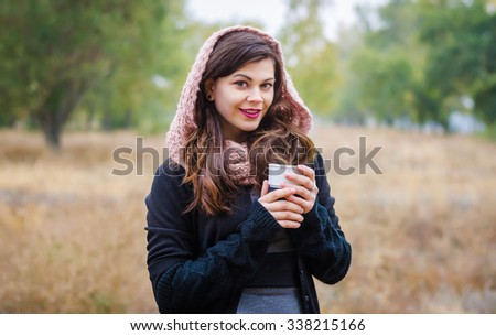 Young smiling girl in a scarf and hat with a cup of coffee (tea) in the hands of autumn outdoors. - stock photo