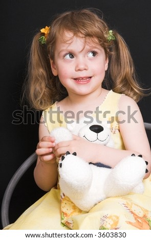 young smiling girl in yellow dress with toy