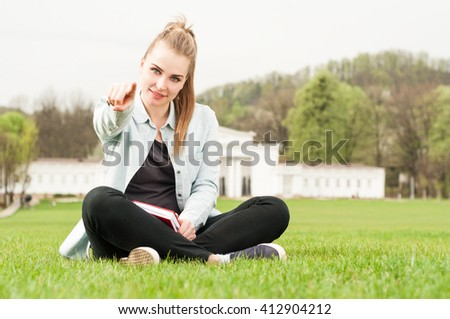Young smiling girl pointing finger at you while sitting on grass in the park and holding a book with copy space - stock photo