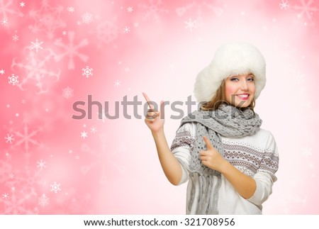 Young smiling girl showing pointing gesture - stock photo
