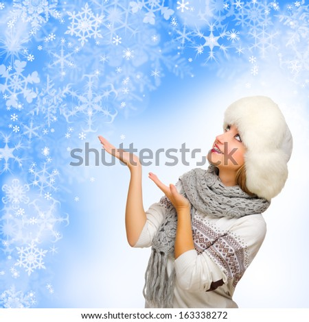 Young smiling girl shows welcome gesture on winter background