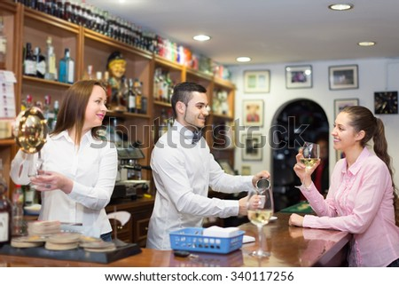 Young smiling girl standing at bar and holding glass of wine. Focus on guy