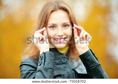 Young smiling girl-student in glasses close up against yellow autumn nature. - stock photo