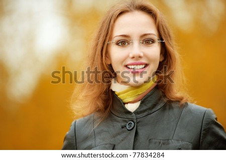 Young smiling girl-student in glasses close up against yellow autumn nature.