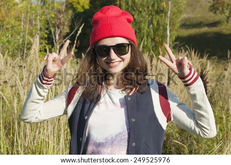 Young smiling girl. Teen girl in the red hat with hands up. Fun teen girl. - stock photo