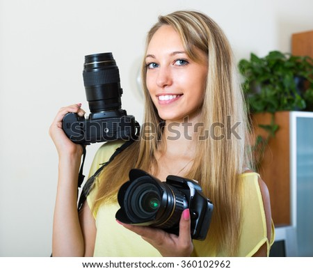 Young smiling girl testing  professional cameras at home
