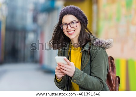 Young smiling girl using her smart phone. She carrying a backpack. - stock photo