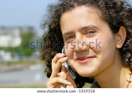 Young smiling girl with cell phone, city in the background is out of focus