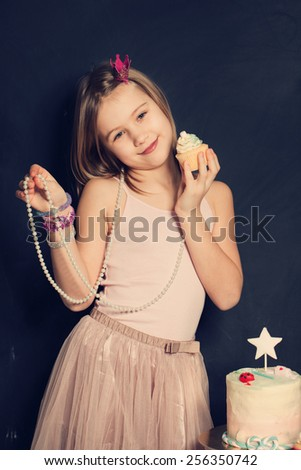 Young smiling girl with cupcake,  birthday card - stock photo
