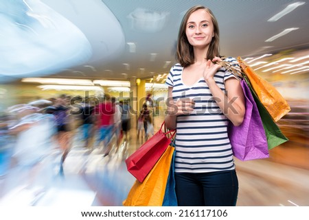 Young smiling girl with shopping bags at shopping mall - stock photo