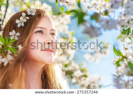Young smiling girl with white cherry flowers in her long hairs looks ahead on a background with spring trees and white flowers. Natural beauty and color. - stock photo
