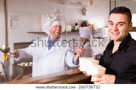 Young smiling handsome guy purchasing fast food in cardboard box at cafe - stock photo