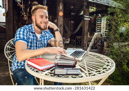 Young smiling handsome man in casual clothes sits at an iron table with computer against country arbor. - stock photo