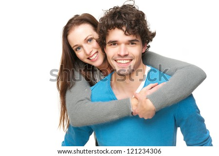Young smiling happy couple isolated on white background. Beautiful laughing young woman is piggyback riding on handsome young man shoulders. - stock photo