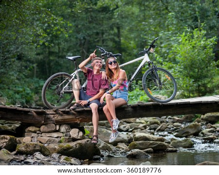 Young smiling happy couple resting in the forest on the river bridge near bicycles and looking up - stock photo