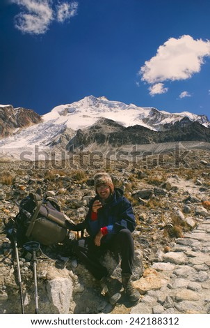 Young smiling hiker resting on its way to Huayna Potosi mountain, peak in Bolivian Andes - stock photo