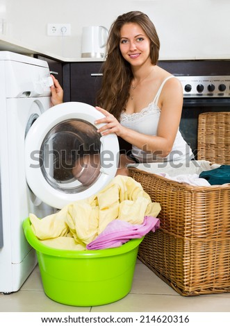 Young smiling housewife using washing machine at home kitchen  - stock photo