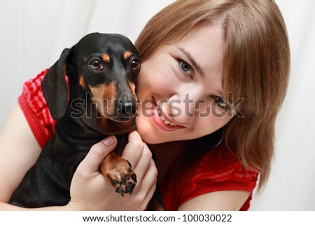 Young smiling lady hugging her Dachshund dog - stock photo