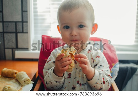 Young smiling little boy eating a pancake