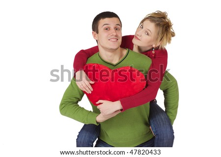 Young smiling loving couple with big red heart in hands
