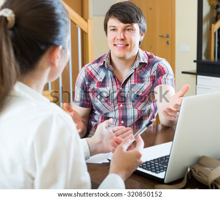 Young smiling man and woman talking with laptop and papers at the table