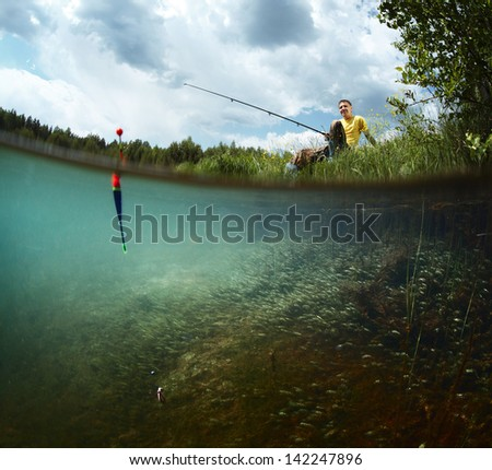 Young smiling man fishing on a green pond's coast with underwater view of weed on a bottom - stock photo