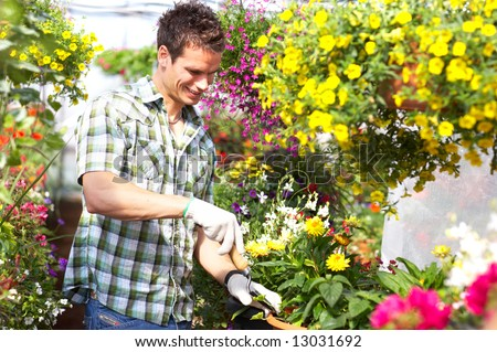 Young smiling man florist working in the garden - stock photo