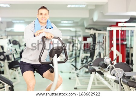 Young smiling man in a gym, resting after cardio training - stock photo