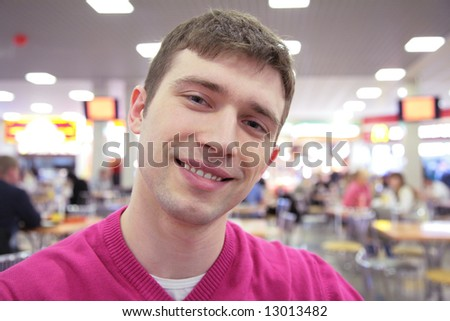 young smiling man in cafe